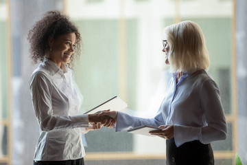 Smiling diverse businesswomen shake hands greeting in office