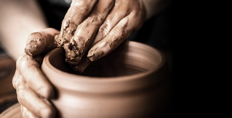 Hands of potter making clay pot on black background