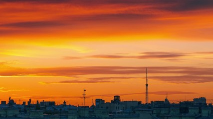 Fotobehang - Epic sunset clouds in orange sky over city skyline. Saint Petersurg, Russia. Zoom out. Timelapse, 4K UHD.