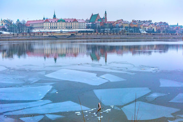 Old Town with reflection in frozen river Vistula River during snowy evening blue hour, Warsaw,...