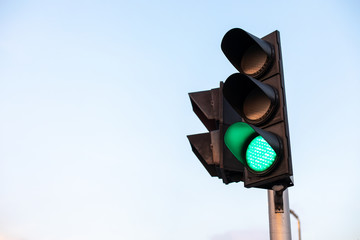green traffic light with blue sky background