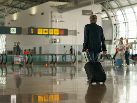 Brussels airport inside image, somebody with suitcase going anywhere. Photography with defocused background.