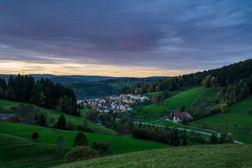 Germany, Idyllic black forest village elzach houses and streets in valley surrounded by fir trees at sunset, view above with red sky