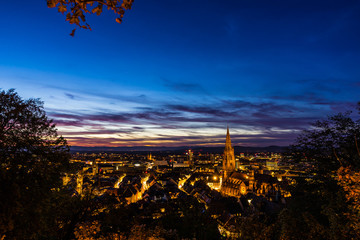 Germany, Famous black forest city freiburg im breisgau in baden, skyline with cathedral after sunset in magical dawning atmosphere from above roofs
