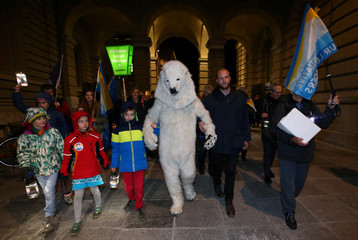 People walk with an activist dressed in a polar bear costume as members of the Swiss Glaciers Initiative committee hand over boxes with signatures supporting a referendum at the Federal Chancellery in Bern