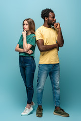 full length view of thoughtful interracial couple standing back to back on blue background
