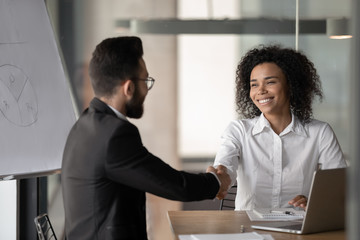 Smiling biracial businesswoman handshake male colleague at briefing