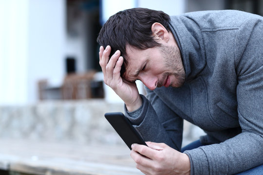 Sad adult man reading bad news on mobile phone in winter