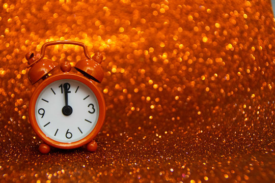 Golden clock to the left of the photo showing midnight on a golden background with a glitter. Copy space for advertising. Copy space area for text. Merry Christmas