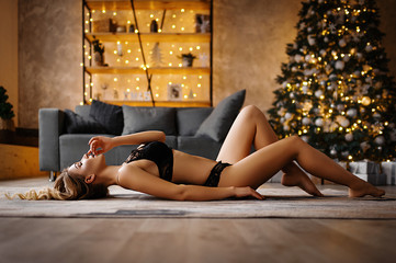 Attractive elegant girl in black underwear near the Christmas tree. Sexy photo of blonde in lingerie for the New Year