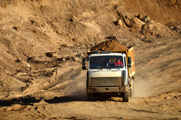 Dump truck transports sand and other minerals in the mining quarry.