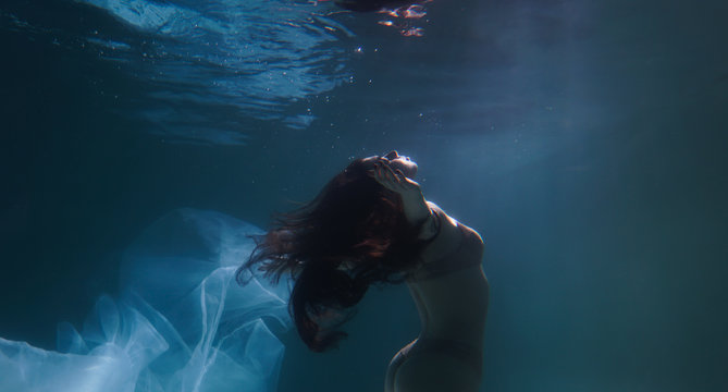 Beautiful girl swims underwater with long hair. Blue or gold background like gold. The atmosphere of a fairy tale or magic. Diving under the water with a shiny cloth