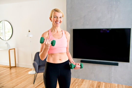 Portrait of fit woman training in her living room with dumbell
