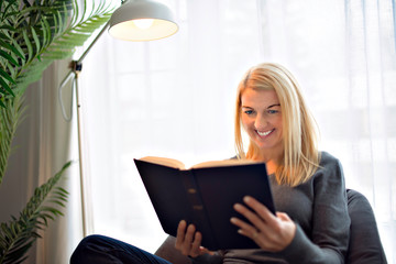 Cheerful blonde woman sitting on her couch reading a book at home in the sitting room