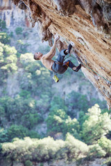 Rock climber looking up on challenging route on overhanging cliff