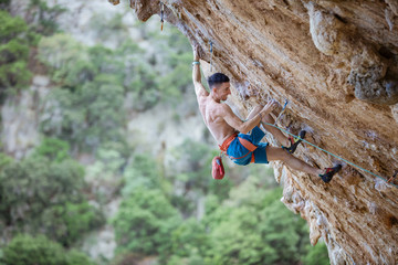 Rock climber on challenging route on overhanging cliff