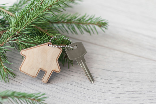 Flat layout on wooden background: figures, house, key and spruce branches / real estate 2020