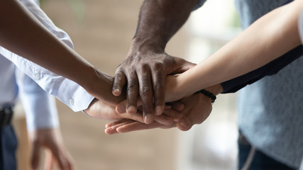 Close up image multiracial people joining hands demonstrating unity.