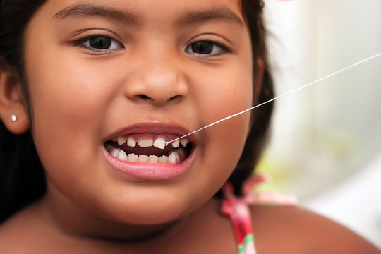 A young latino girl demonstrating how to pull out a loose baby tooth by tying a string to the central incisor.