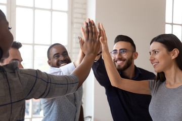 Overjoyed multiracial young business team members giving high five