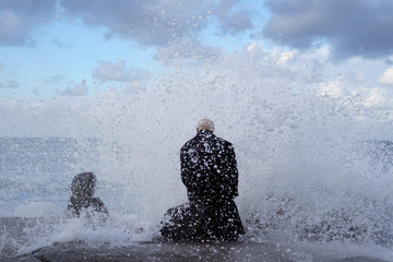 Dressed in a long wool trench coat Bruce Parker sits on a rock enjoying the waves spraying him as they crash on the beach during the arrival of a winter storm in Oceanside