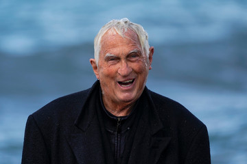 Dressed in a long wool trench coat Bruce Parker reacts with a smile as he enjoys the spray of waves as they crash on the beach during the arrival of a winter storm in Oceanside
