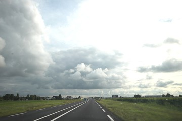 Big grey cumulus clouds above regional road N219 in the Zuidplaspolder at Zevenhuizen