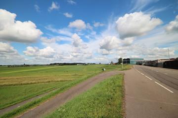Dutch landscape with industries along the dike of river Hollandsche IJssel, meadows in the low Zuidplaspolder