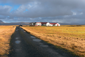 Narrow gravel road with potholes to a farm in the countryside of Iceland under stormy sky