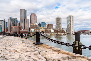 View of Boston skyline from cobbled harbourside footpath in foreground on a partly cloudy autumn morning