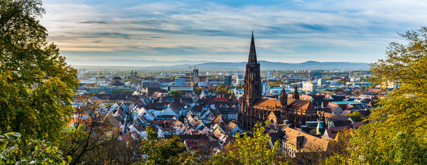 Germany, XXL panorama of city freiburg im breisgau skyline with cathedral muenster in old town in warm sunset light in romantic autumn season, aerial view above cityscape Fototapete