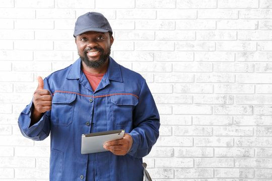 African-American car mechanic with tablet computer showing thumb-up near brick wall