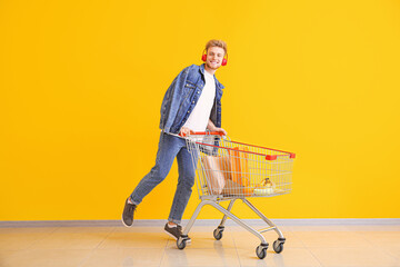 Foto op Plexiglas Muziekwinkel Young man with shopping cart near color wall