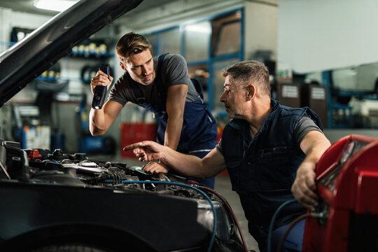 Two mechanics talking while repairing car's AC unit in auto repair shop.