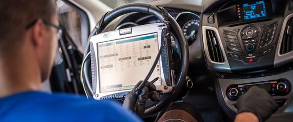 Automobile computer diagnosis. Car mechanic repairer looks for engine failure