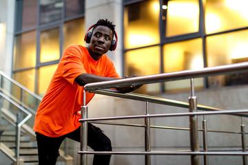 african-american man in stylish orange hoodie sweatshirt in wireless headphones listening music...
