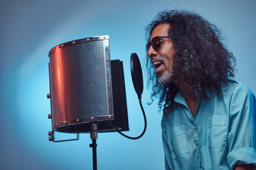 African vocal artist sings a song loudly next to a microphone condenser. Isolated on a blue background.