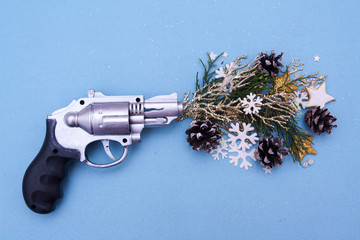 Holiday shot with a gun. Toy gun charged with Christmas mood on a blue background. Beginning of the New Year holidays. Art, creative for the new year