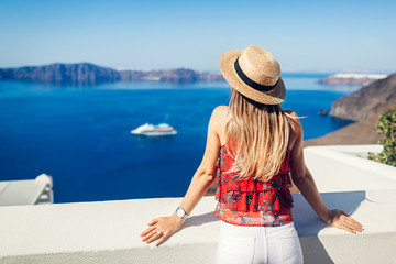 Woman traveler looking at Caldera from Fira or Thera, Santorini island, Greece. Tourism, traveling, vacation concept Fotomurales