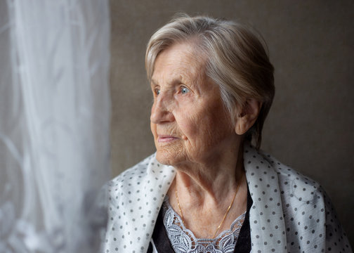 Old woman looks out window, sad, remembers, thinks. Closeup portrait