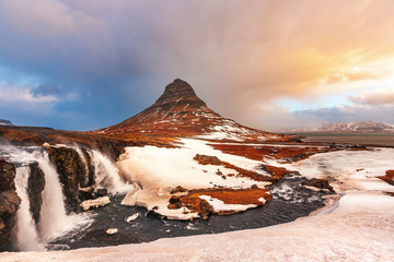 Famous mountain with waterfalls in Iceland, windy weather, kirkjufell, winter in Iceland, ice and snow, reflections, yellow grass, nature, icelandic famous landscape