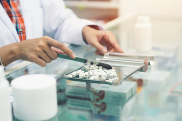 Medicine tablets on counting tray with counting spatula at pharmacy