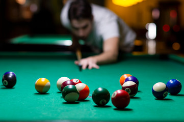 Young man playing pool in pub