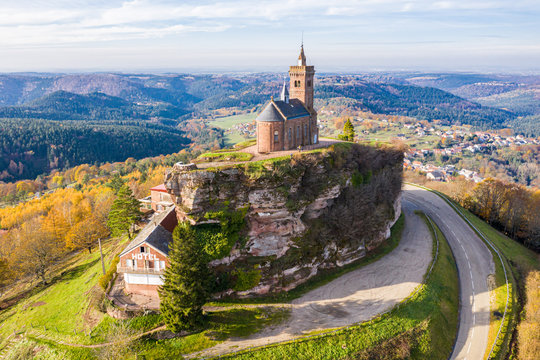 Beautiful autumn aerial view of St. Leon chapel dedicated to Pope Leo IX atop of Rocher de Dabo or Rock of Dabo, red sandstone rock butte, and Moselle-Vosges mountains and valleys. Lorraine, France