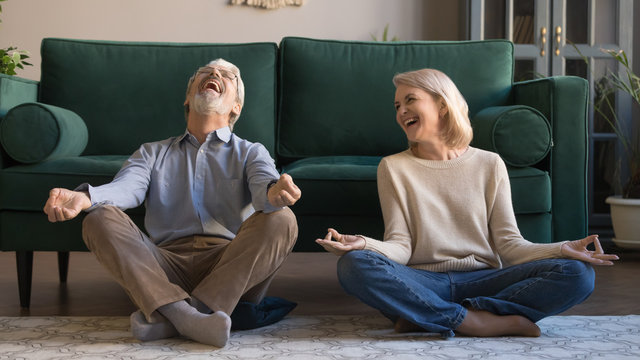 Laughing aged spouses sitting on floor in lotus position