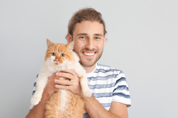 Man with cute cat on light background