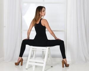 young woman in black sitting on a chair, legs apart back view