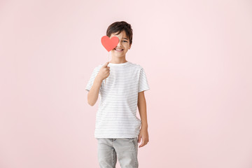 Cute little boy with paper heart on color background. Valentines Day celebration