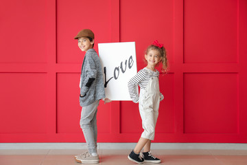 Cute little children holding picture with word LOVE on color background. Valentines Day celebration