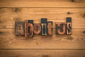 About us, phrase written with vintage letterpress printing blocks on rustic wood background
